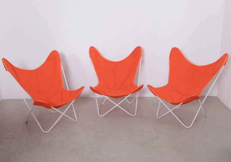 Old iron frames with orange cloth sling seat covers. Clean and room ready, circa 1958.