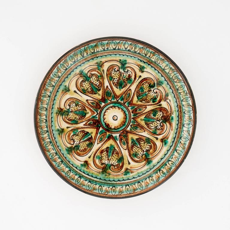 These terracotta serving plates were all handmade in the 20th century. They have a glaze finish and beautiful decorative patterns to embellish them. The three terracotta-color set are from Sweden and have ivory patterns circling the exterior rim of