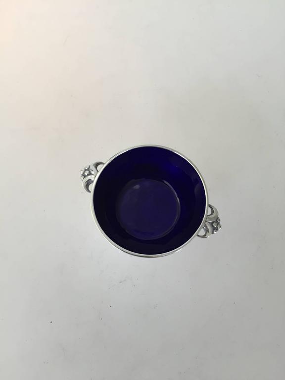 Evald Nielsen sterling silver salt dish with blue enamel. The salt dish measures 5.8 x 1.9cm and is in a good condition. Marked: Sterling Silver, Evald Nielsen, Denmark.  Evald Nielsen (1879-1958) was a Danish silversmithy. Evald Nielsen opened