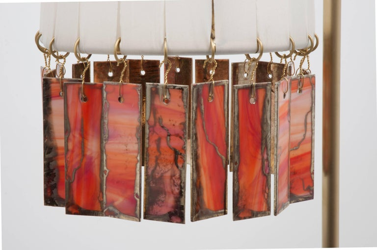 Magic is a standing lamp entirely handmade and manufactured by hand, in Tuscany, Italy.  The lampshade and the metal body stem of this light object and are made of brass with mat finish.  The lampshade is wrapped with acrylic silk strips or