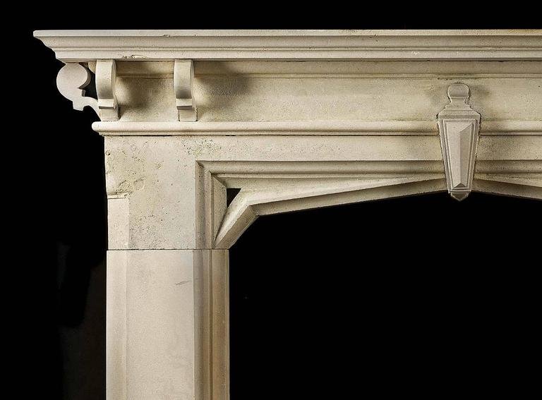 A Victorian Gothic Revival limestone antique fireplace surround with a small central keystone linking the frieze to the arched opening and a shelf supported on six small brackets.