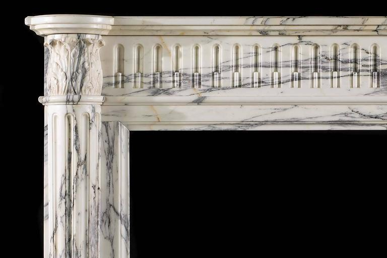 A small compact Louis XVI antique fireplace in elegantly veined Arabescato marble. The simple shelf rests over a carved stop-fluted frieze, flanked by acanthus leaf capitals supported on half round pilasters,