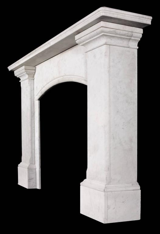 A large elegantly simple Regency fireplace mantel in the Egyptian Revival manner carved in Carrara marble. The moulded rectangular shelf supported by stepped capitals above chamfered tapering jambs and with a 'slow' arched opening.  Scottish,