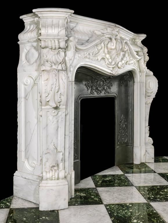 A rare, monumental and highly ornate Louis XV style deeply carved statuary marble antique fireplace surround with it's original cast iron insert. The upper stop fluted coffered frieze sits above and behind an enormous and most elaborately scrolled