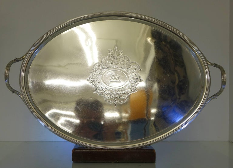A very elegant large oval silver tea and coffee tray. The tray has a reeded border and a very beautifully engraved cartouche. Inside the cartouche is a family crest of a unicorn. The handles of the tray are applied and have been raised for easy use.