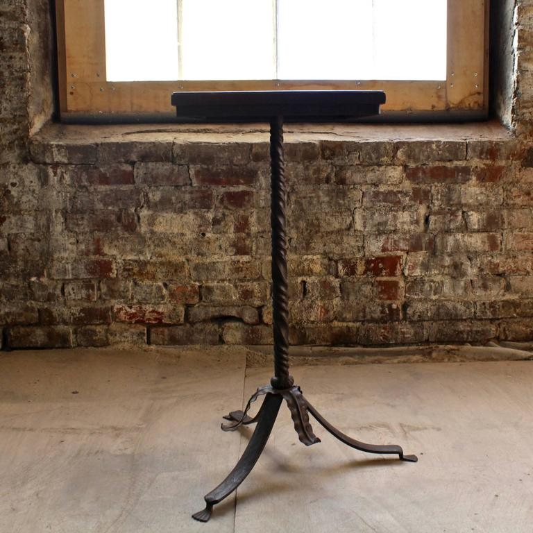 A walnut top side table with a Neo-Gothic wrought iron base.  The base has a twisted pedestal support resting on a knob with applied lifework and three sabre legs with fluted feet. There is hammered work to each leg.  The walnut top has an