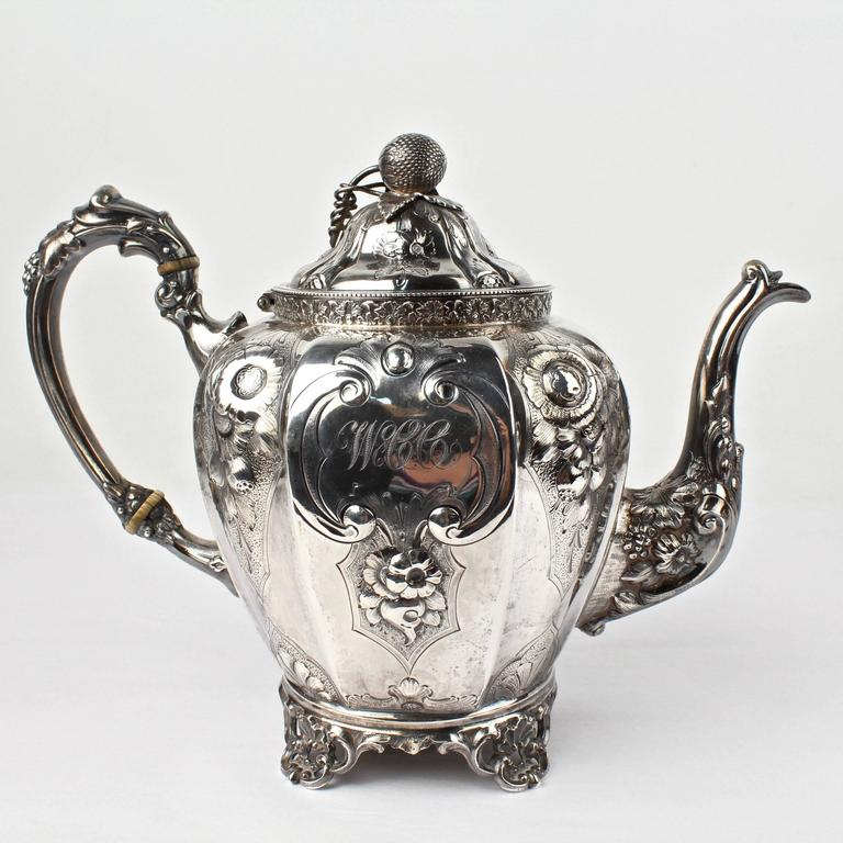 A large, four-piece, 19th century American coin silver tea set by the renowned New York silversmiths, Wood & Hughes. A stately and impressive set.  Finely worked with repousse decoration throughout. The central cartouches each bear an early