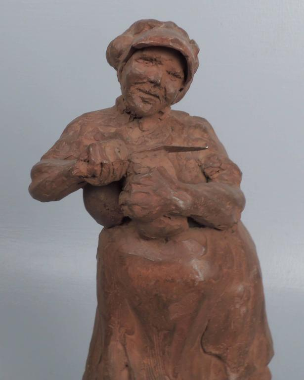 A ceramic sculpture of a rotund woman slicing bread by the Cuban-American sculptor, Roman Lago.  Height: circa 13 1/4 in.  Items purchased from David Sterner Antiques must delight you. Purchases may be returned for any reason for a period of 7