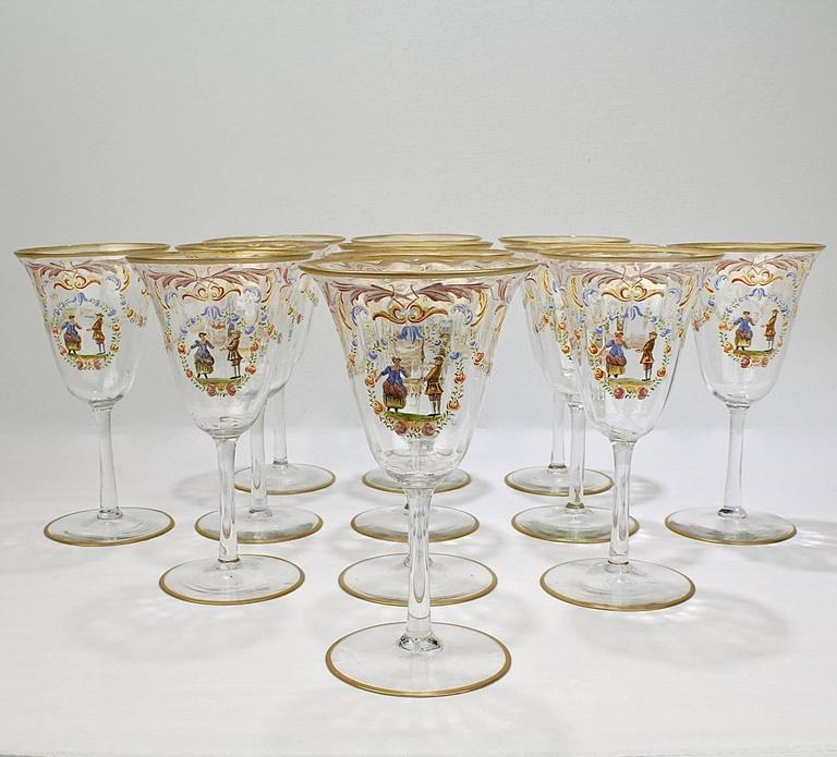 A full set of 12 enameled Italian or Venetian glass water goblets or wine glasses.   With polychrome Florentine enamel decoration, a central cartouche bearing a peasant couple surrounded by a wreath with rose, and gilded feet and