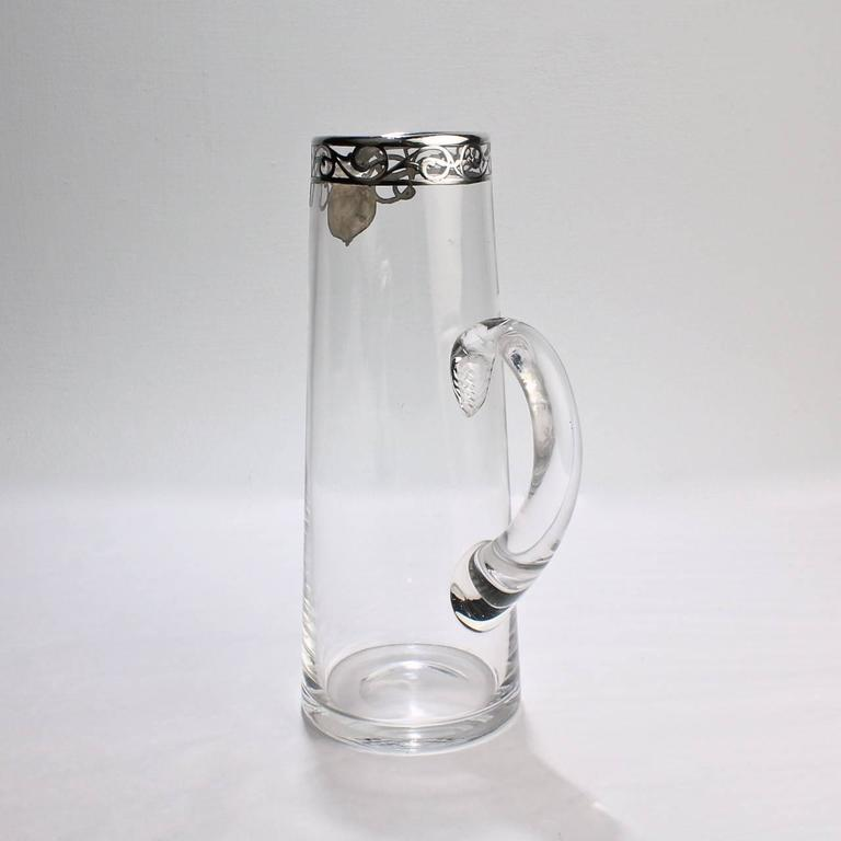 An early 20th century Art Noveau silver overlay glass cocktail pitcher.