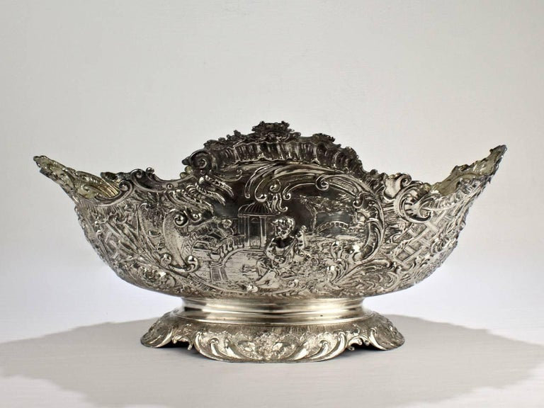 A large-scale, extremely ornate 19th century Rococo Revival solid silver bowl or centrepiece.   Constructed of worked and fused sections each having large cartouches.   Each cartouche has scenes of cherubs and a faux basket weave decoration.   The