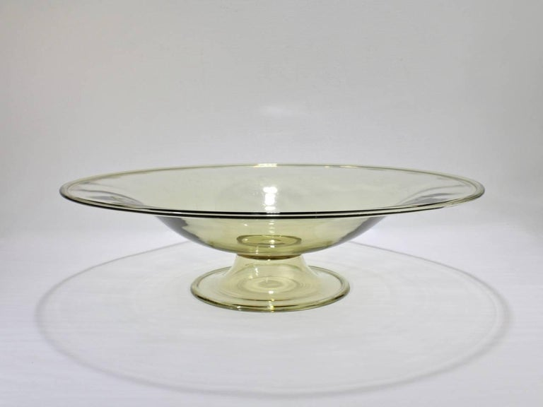 A very large midcentury Murano or Venetian amber color glass footed bowl.  Perfect as a table centerpiece.  Likely by Salviati.  Measure: Diameter ca. 16 3/4 in.  Items purchased from David Sterner Antiques must delight you. Purchases may be