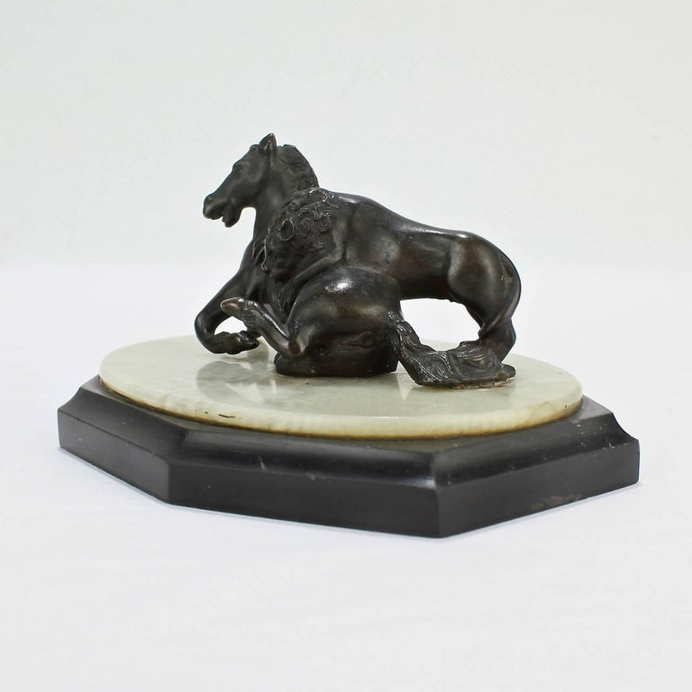 A fine 19th century Grand Tour miniature model of the Lion Attacking a Horse sculpture.  Modeled after the ancient Roman version found on Capitoline Hill.  Sized as a paperweight for the desk or perfect for shelf nestled amongst leather books