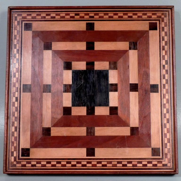 This is a fine handmade inlaid wooden game board. The front is for checkers and chess. They reverse is a starburst pattern and is probably for some variant of parcheesi. Made of mahogany, ebony, rosewood, and satinwood. Dates to the early to