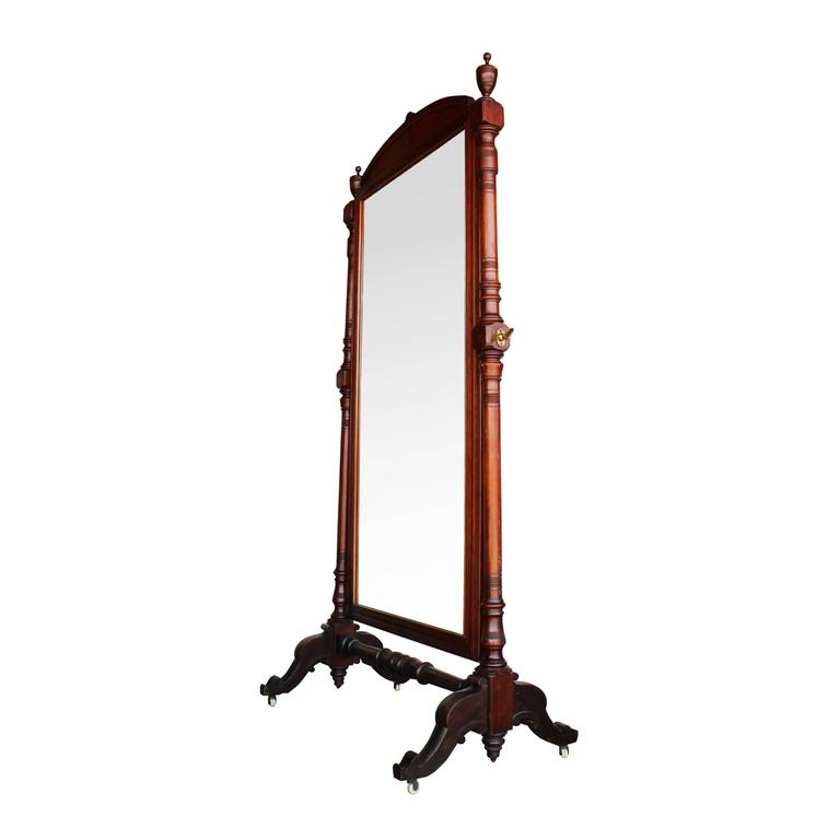 This elegant late 19th century mahogany cheval mirror features plenty of turned details on each supporting arm, brass hardware, and four porcelain casters for mobility. Urn finials and an arched header add flourished of additional detail to this