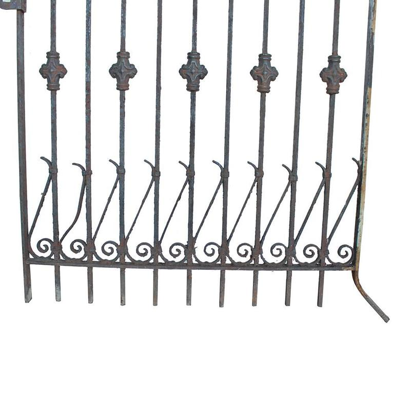 """A balancing act of arrows, curlicues, and medallions adorn this wrought iron gate with cast details. Perfect late Victorian style with an unusual 77"""" height."""