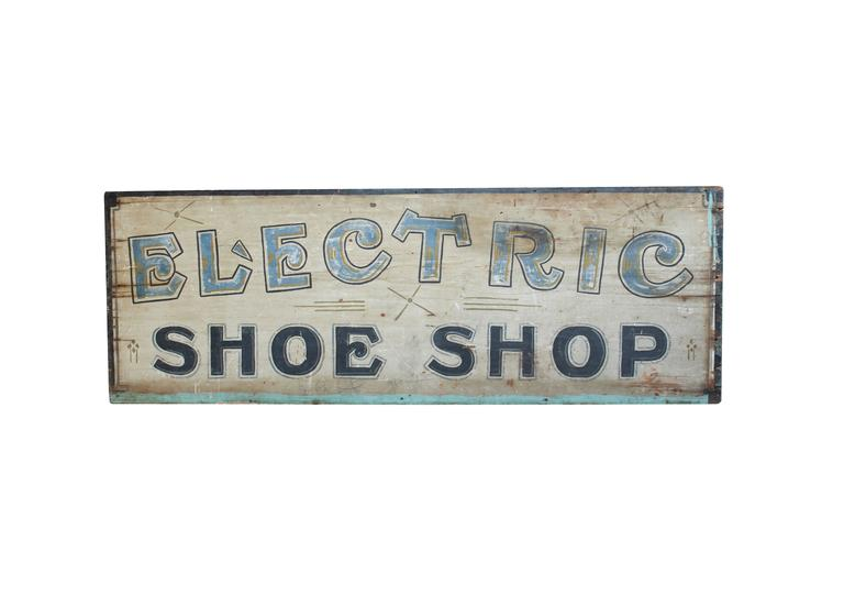 This unique Electric Shoe Shop wood sign is hand-painted and double-sided. With a bold font reminiscent of turn-of-the-century styles, the pale blue, navy, green, and gold colors are still vibrant. The slight variations in the green accents on