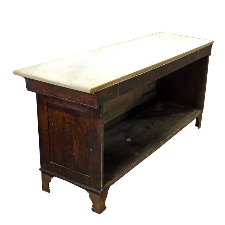 The Bernard Gloekler Company was founded in Pittsburgh, PA in the late 19th century and had a thriving business manufacturing butcher and grocer's equipment and supplies. This solid oak marble topped case has an opalite glass front panel and