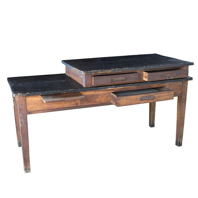 This fun and rustic dual-tier table came from the Mt. Angel Benedictine Convent and dates to the 1930's. Used as a work table by the sisters, the tiered construction is visually interesting and makes for a fun piece of furniture. The black tabletops