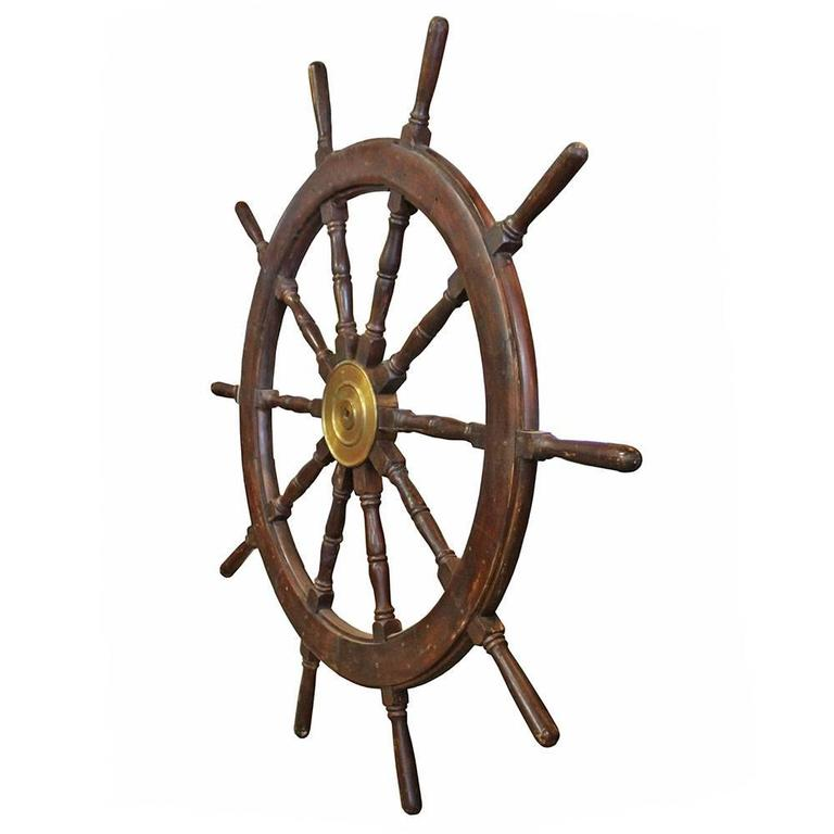Solid hardwood ship's wheel with ten spokes and a brass fitting. American made, the spokes of this massive ship's wheel feature turned details making it an impressive accent piece in any setting.