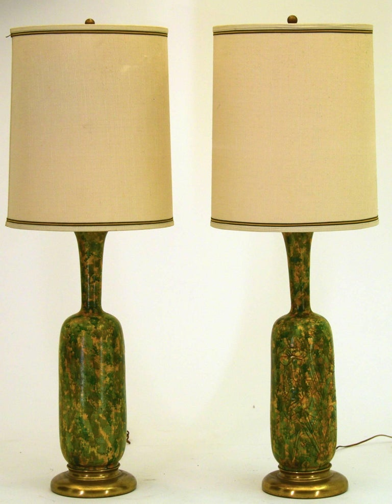 A unique pair of very large table lamps by Marbro. The ceramic vessels are mounted on gold gilded colored bases. The ceramic lamps have either a painted or glazed finish over them that resembles the famous sponge ware of the 1920s. On one side of