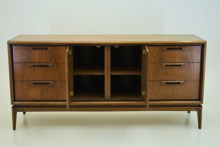 Not clearly marked, it is either produced by Lane Alta Vista or the Broyhill company.  A singular sideboard with modernist lines and quality black walnut throughout. Note the good depth of this unit making proper storage a breeze.  Measures 66