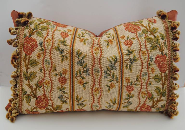 Custom pillow cut from an antique French needlepoint fragment from late 1800s. Hand worked in silk and wool with good color. Minor thread loss, shown in photo but not detracting from the design. Pillow is edged with Scalamandre silk tassel trim and