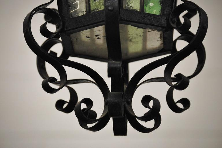 French hand forged iron lantern with colorful stained glass panel inserts, early to mid-20th century. Very nice scrolling iron work. The lantern has been newly wired for a single bulb.