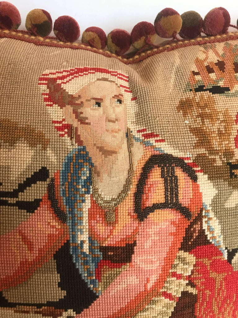 Custom one of a kind pillow cut from an antique English needlepoint tapestry. Very fine work on the detail of the faces with metallic beading. Minor loss of wool in background area due to age of piece. Tapestry is trimmed with designer wool ball
