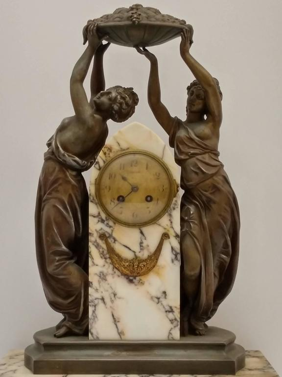 French Art Nouveau sculpture with a clock decorated with a pair of women rejoicing in the harvest of the season.