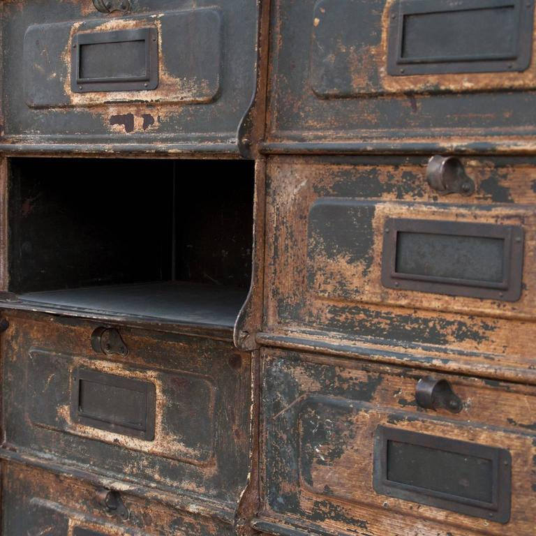 One of a kind metal cabinet case with thirty slots, originating from the industrial revolution, in great functioning condition with original patina. Features original metal emblem of manufacturer