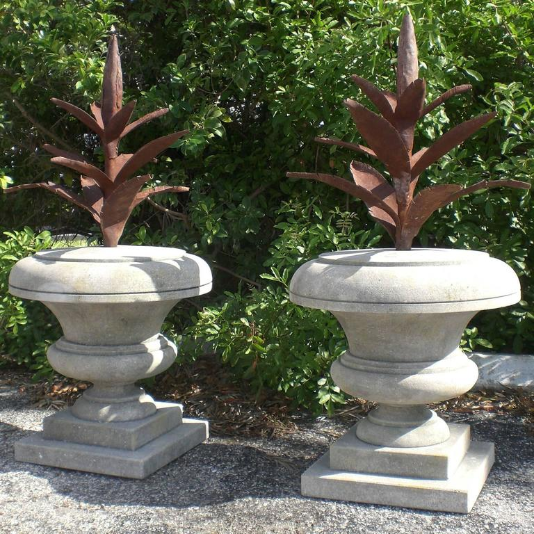 A  pair of very decorative hand carved limestone finials topped with metal leaves in the shape of an agave raising from the urns. Wear consistent with age and use. Circa 1940-1950 Orvieto, Italy.