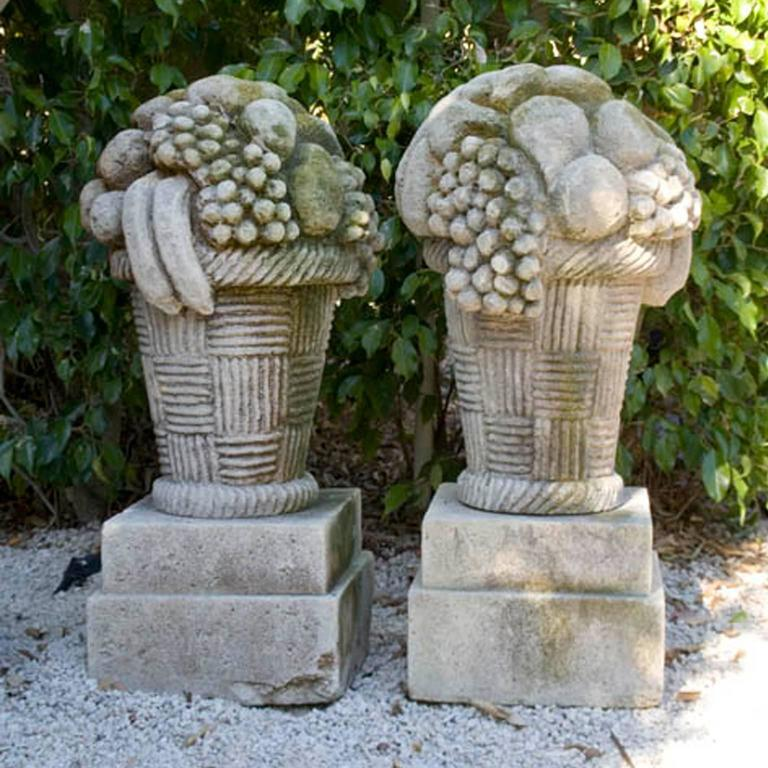 A pair of fruit basket finials hand carved in French limestone are positioned on the original small square plinths. Wear consistent with age and use. Circa 1930, Chateau St. Cyr, France.