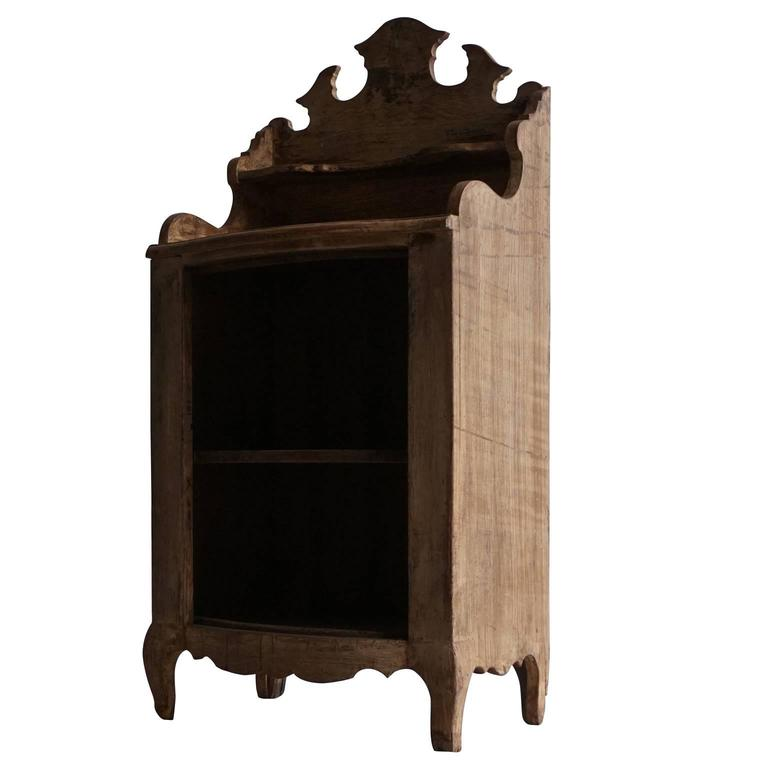 Petit and charming Rococo bookshelf or nightstand with a decorative arched back, was carved in pinewood, circa 1750. This small cabinet was in a farm house, in Dresden, Germany.