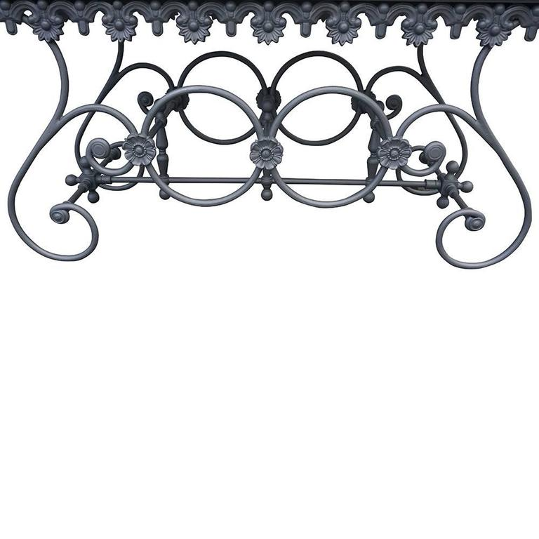 A rectangular butcher table with a cast iron and wrought iron base, richly decorated with rosettes and scrolls. The base is topped with a white Carrara marble table top. Wear consistent with age and use, circa 1960, France.