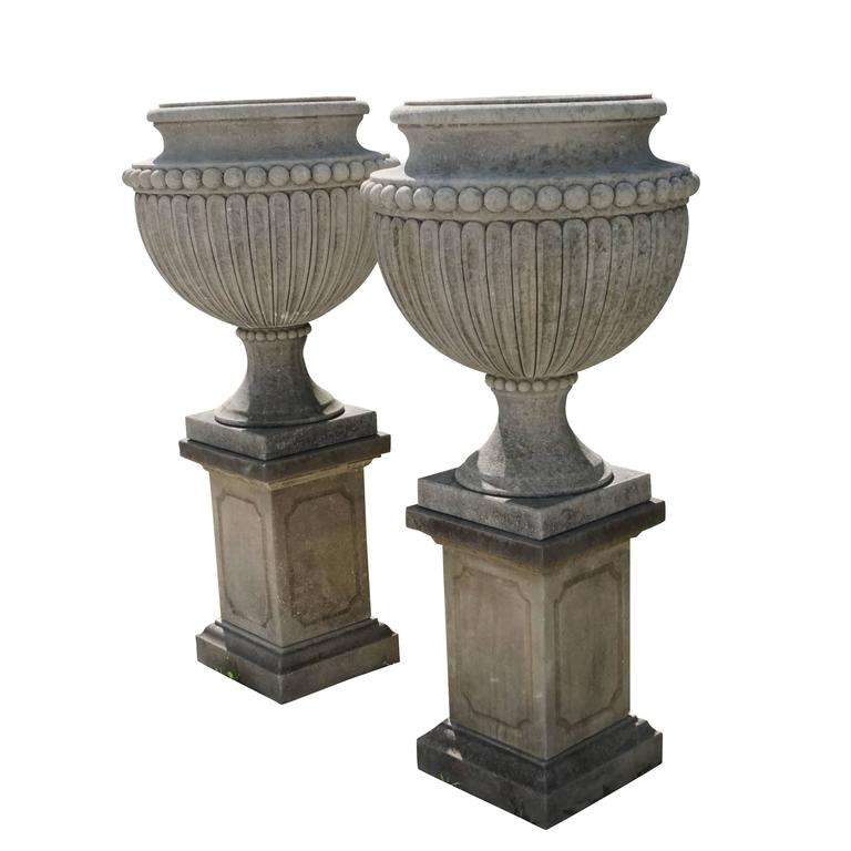 "A pair of limestone urns "" Vases aux Gouttes ""on original square pedestals with a fine bevel. The garden urns have a lobed ovoid body and are positioned on a circular foot with a square base. Wear consistent with age and use.  Urn: 32.5″ H  Base of"