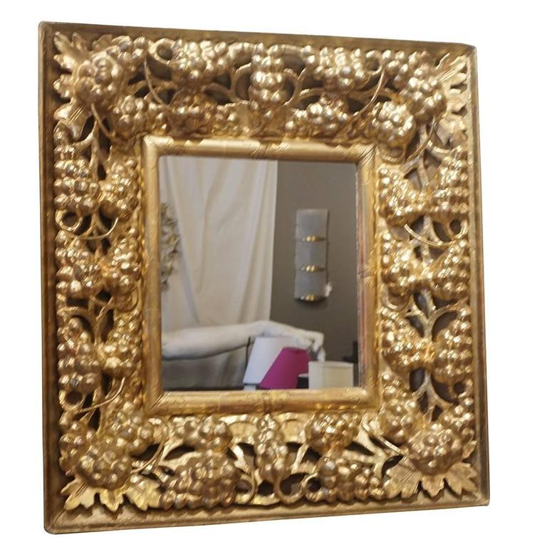An antique, very richly Italian hand carved mirror with a gilded wooden frame, adorned with grapes and foliage and original mirror glass, in good condition. The small mirror represents the Baroque time period. Wear consistent with age and use, Circa