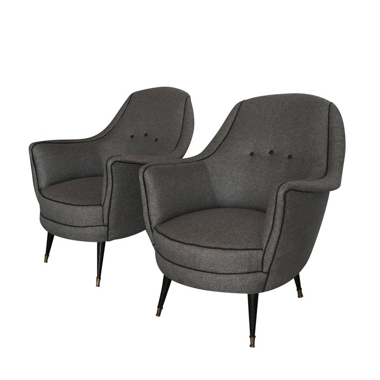 A vintage Mid-Century Modern Italian pair of lounge chairs with an angular form, buttoned back and seat cushions. The pair are upholstered in a grey denim linen fabric, in good condition. The angled feet are made out of black painted metal and brass