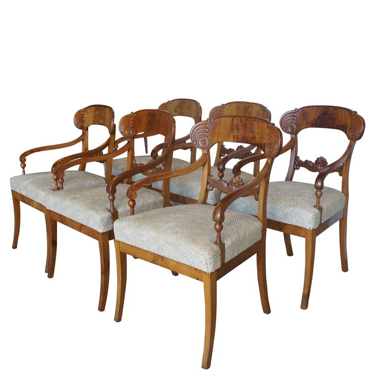 A set of six Karl Johan armchairs from ca. 1830 Malmo, Sweden. The chairs are made of birchwood with shovel-shaped backrests, recessed volute arms, and newly upholstered seats and saber legs. Wear consistent with age and use, some minor repairs.