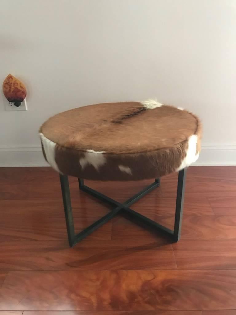 Round upholstered bench having cowhide supported on bronze washed metal base.