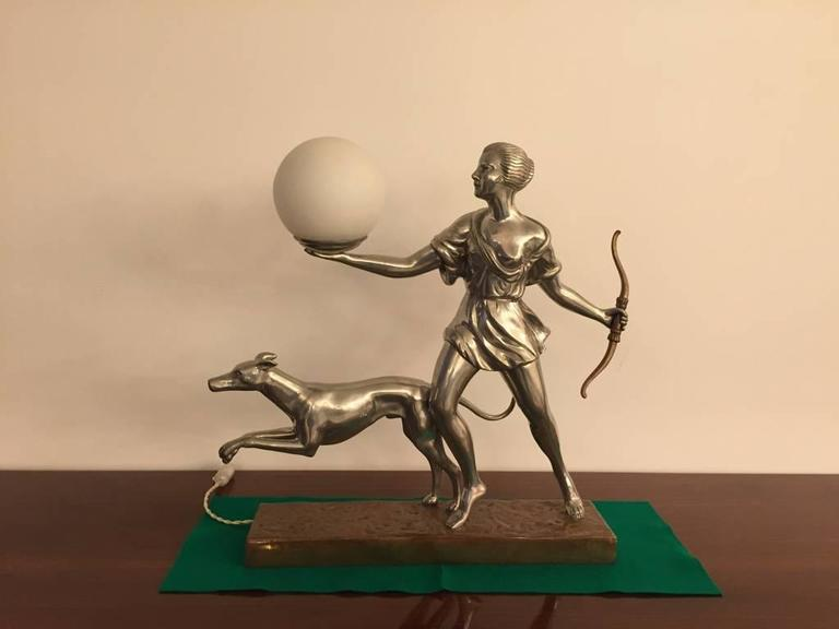 Beautiful French Art Deco table lamp of hunter and dog in nickel with copper base. Stunning details from the bow all the way to the dog. Globe lights up.   2/300 signed by vincent