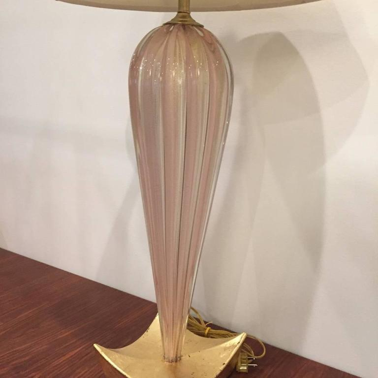 A stylish pair of Mid Century Modern pink Murano glass table lamps with a gold base.
