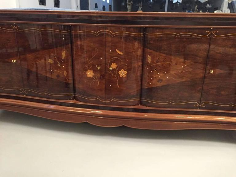 Gorgeous French Art Deco six-door buffet in the style of Jules Leleu. With beautiful Rosewood and mother-of-pearl inlay along with stunning marquetry. The middle doors open to reveal a bank of draws while the outer door reveal shelfs. Having