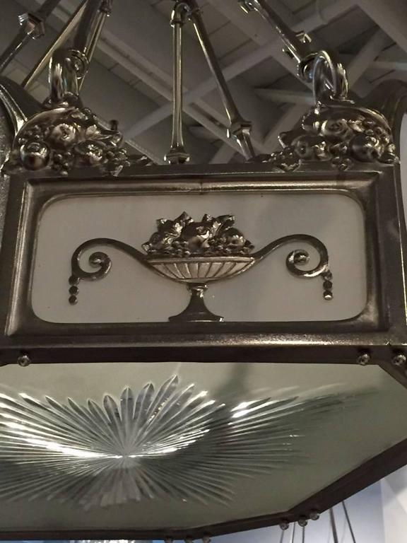 French Art Deco nickel-plated bronze chandelier. Having milky white glass and floral motif. Very elegant adding the perfect Deco decor to your home. Giving off beautiful amount of light.