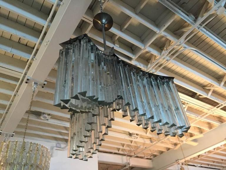 Mid-Century Modern Italian chandelier by Venini. Each of the prisms is solid glass, measuring 11 inches and 4 inches. They hang from hooks onto a chrome frame, as pictured. Any amount of chain can be added for custom hanging length of the chandelier.