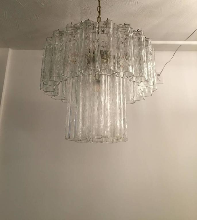 Mid-Century Modern Italian Tronchi chandelier. Each Tronchi is solid glass, measuring 12 inches and 8 inches. They hang from hooks onto a brass frame, as pictured. Any amount of chain can be added for custom hanging length of the chandelier.