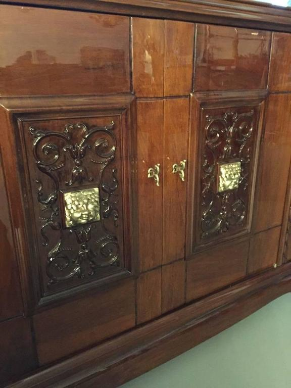 Stunning French Art Deco bronze face walnut credenza. This sideboard has been professionally refinished having a very high French polish. The two center doors have a floral bronze face with beautiful deco details. Inside one of the doors there's a