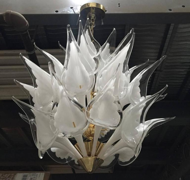 Stunning Italian Mid-Century Modern calla lily flower chandelier by Camer. This high quality fixture has lily shaped pieces of handblown white and clear glass that are installed on a brass frame. The original ceiling plate is included. 