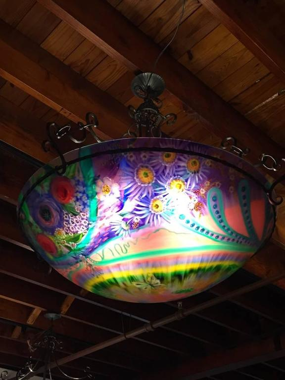 This gorgeous original Ulla Darni 34 inch chandelier is reverse painted on glass with hand-forged iron work. Ulla starts with a blank glass surface to paint on. She uses vibrant colors that pop off the glass, making it feel like the chandelier is