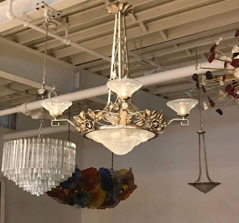 French Art Deco chandelier signed by P. Maynadier. With four opalescent glass shades surrounding a centre opalescent bowl having intricate floral motif details throughout. Shades are held by silvered design frame.